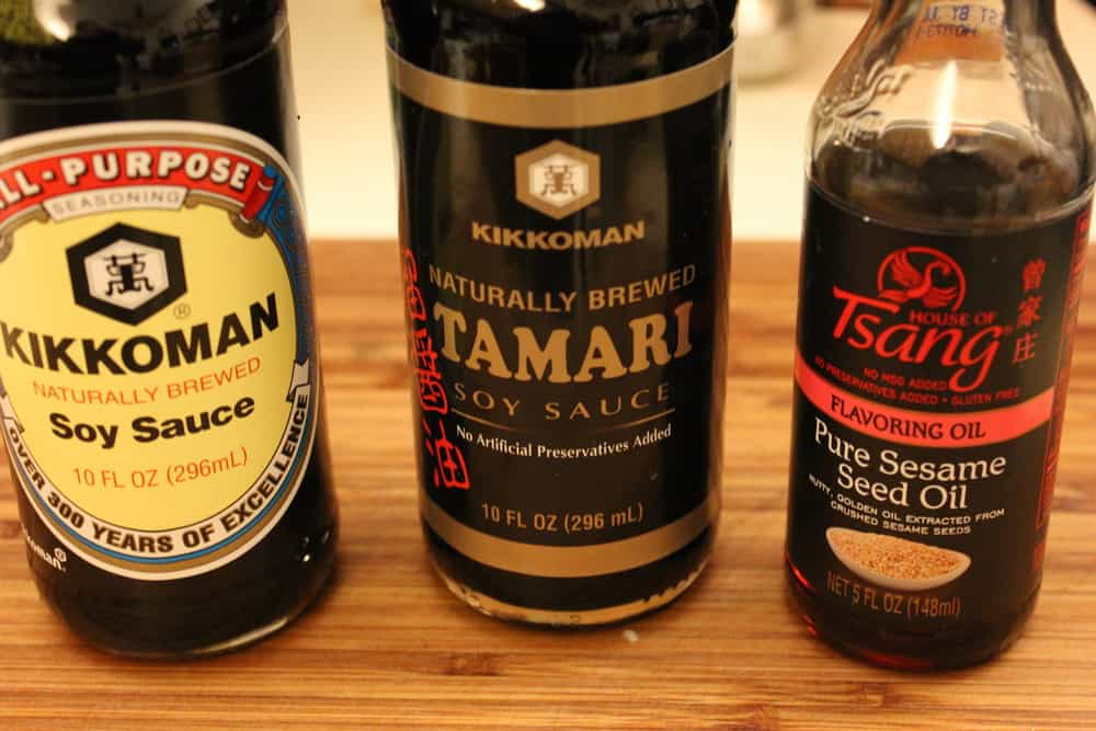 Classic dumpling sauces in bottles on a cutting board, including dark soy, Tarmind, and oyster sacue.