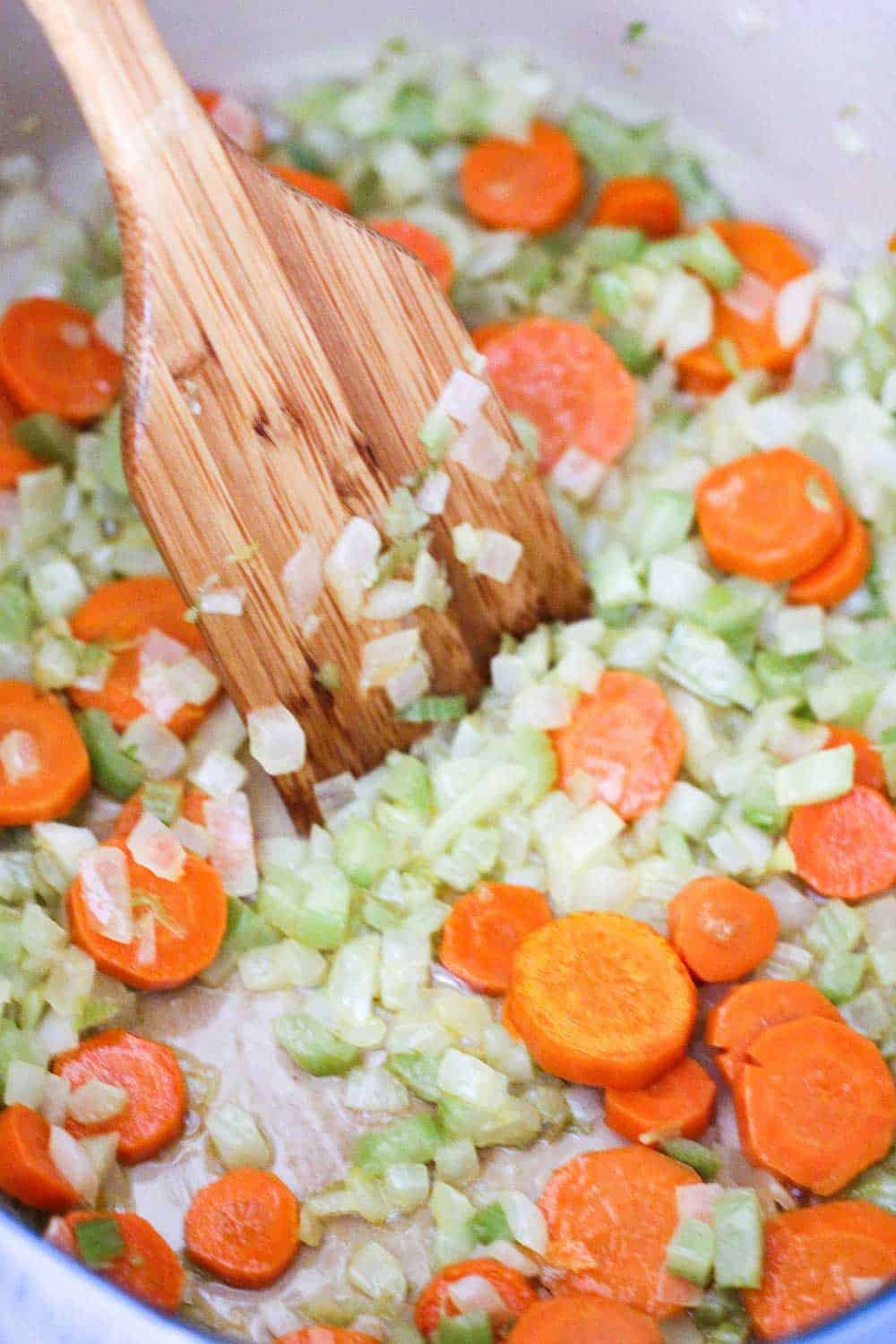 Sliced carrots, celery and onion sautéing in a large pot with a wooden spoon.