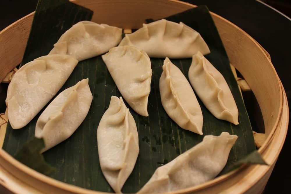 vegetarian steamed dumplings sitting on banana leaves in a bamboo steamer.