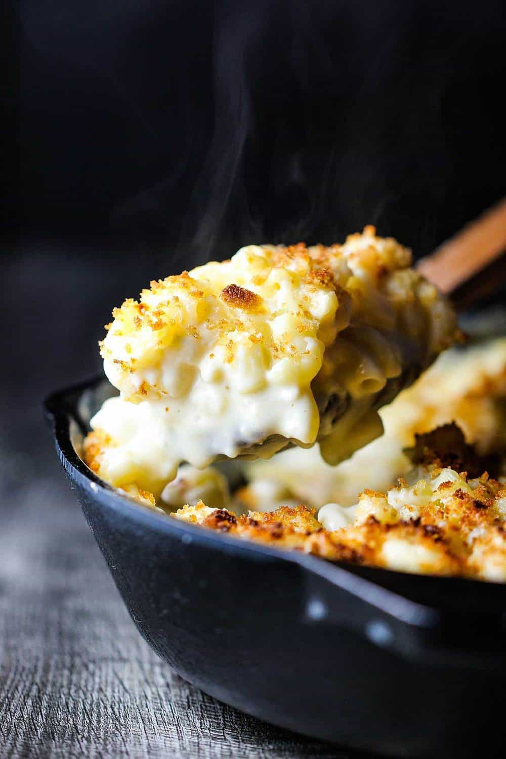 A wooden spoon lifting a helping of ultimate macaroni and cheese from a black cast iron skillet