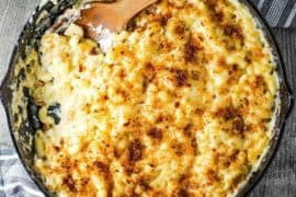 The Ultimate Macaroni and Cheese in a large cast iron skillet with a wooden spoon.