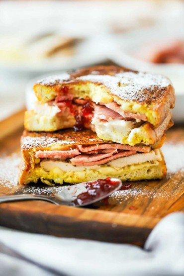 A Monte Cristo sandwich that has been cut in half and is stacked with a bite taken out of the center of it.