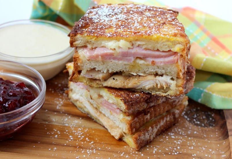 The best-ever Monte Cristo sandwich with Mornay sitting on a wooden cutting board.