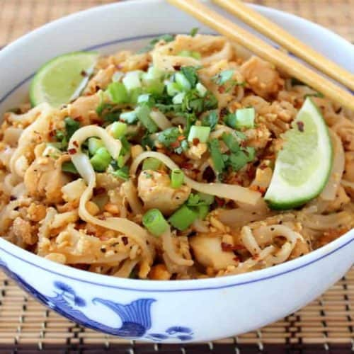 A festive Asian-Classic Pad Thai with Chicken in a white bowl with chopsticks on top of a bamboo place mat