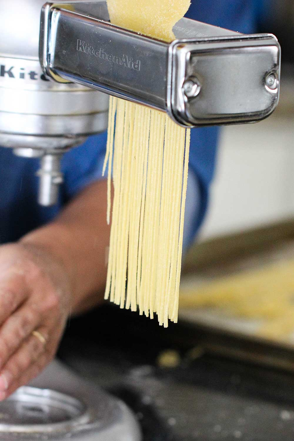 Pasta dough being cut by a pasta attachment on the side of a stand mixer.