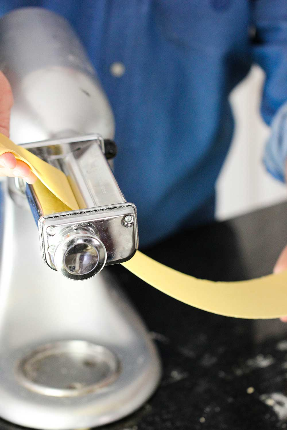 A sheet of homemade pasta being put through a pasta roller on a stand mixer.