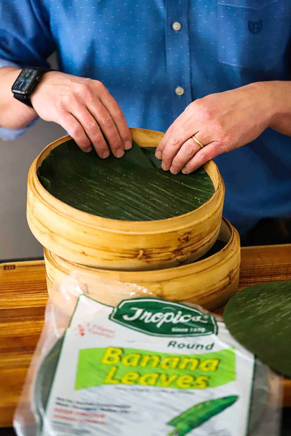 A person placing a circular piece of banana leaves into a double-stacked bamboo steamer with the package of banana leaves in the foreground.