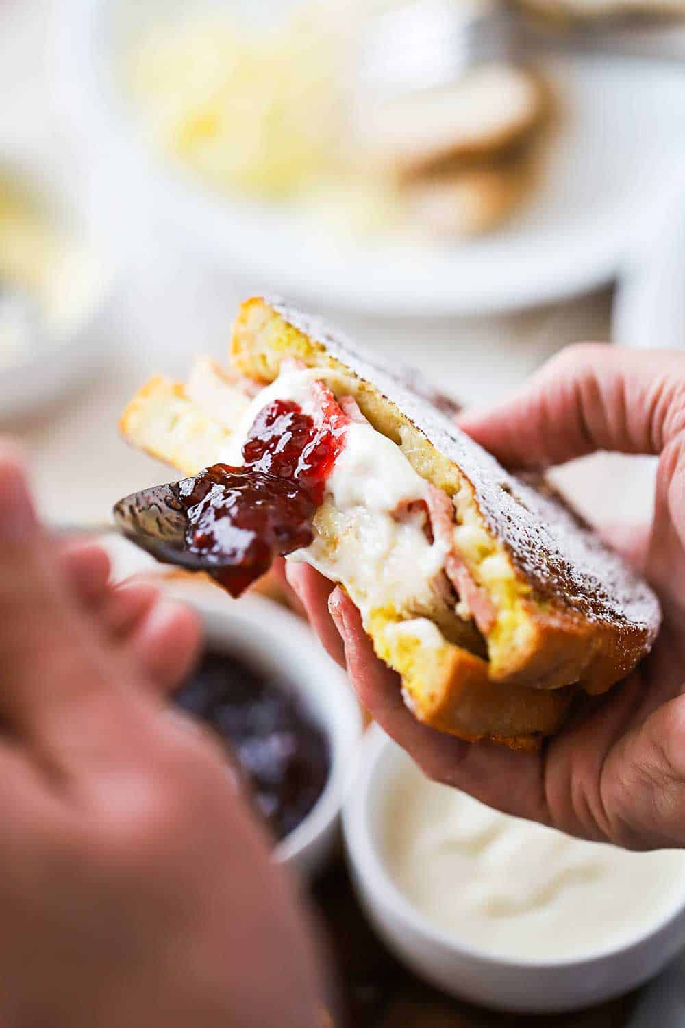 A person using a spoon to spread preserves along the cut side of a monte cristo sandwich.