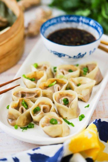 Vegetarian Steamed Dumplings on a white oval platter with a small bowl of hot and sweet dipping sauce next to it.