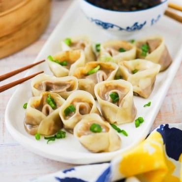 An oval white serving platter filled with vegetarian steamed dumplings sprinkled with chopped parsley.
