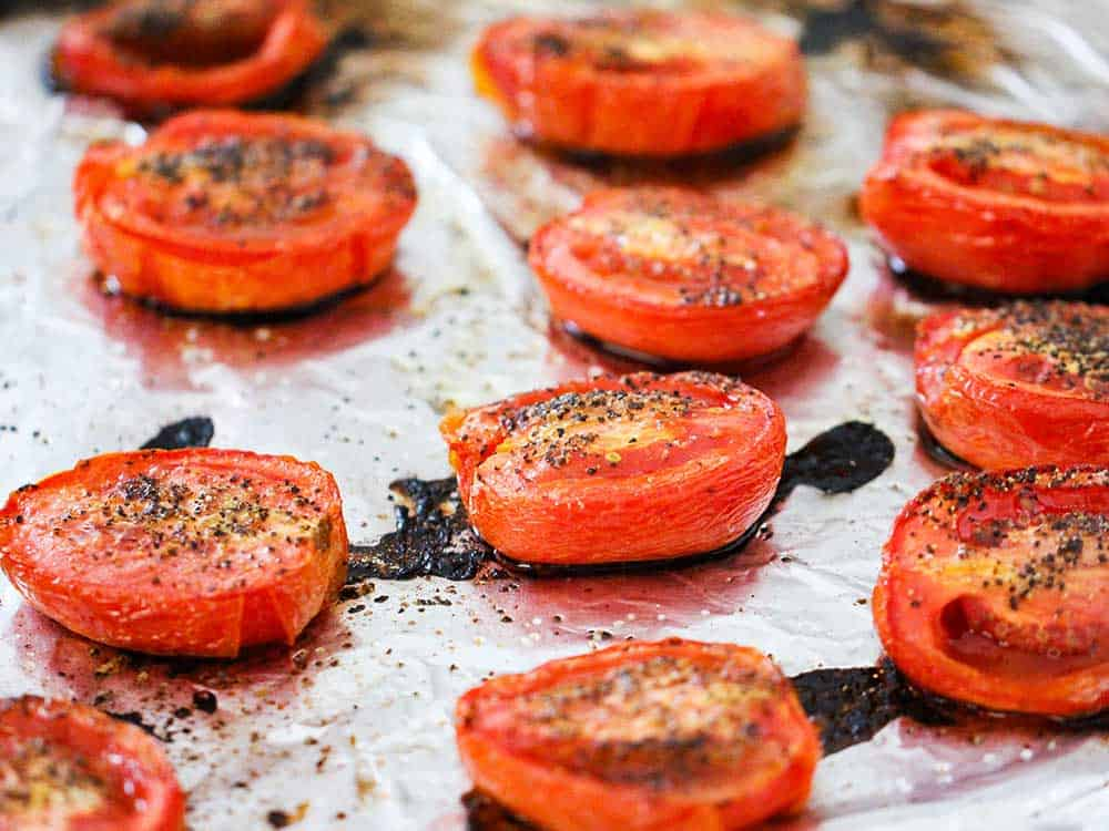 A baking sheet lined with foil with roasted tomatoes on it.