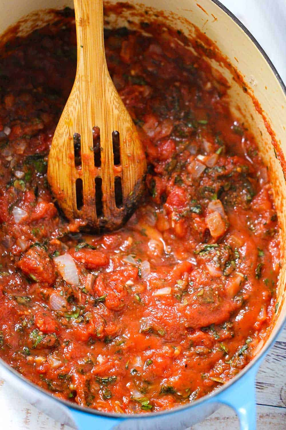 A large blue Dutch oven with tomatoes and herbs simmering in it with a wooden spoon in the pot.