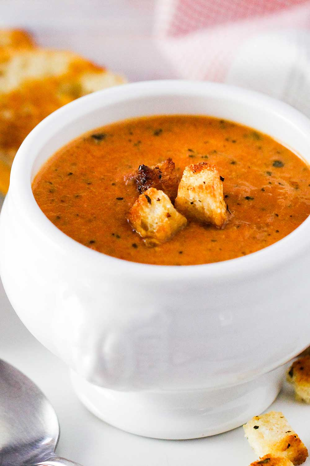 A white bowl of roasted tomato basil soup with croutons on top.