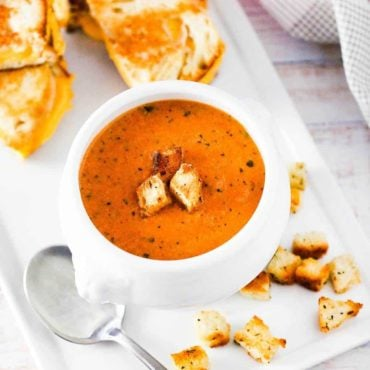 A white soup filled with roasted tomato basil soup next to sliced grilled cheese sandwiches.