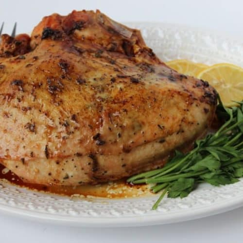 Whole roasted turkey on a white plate with a fork