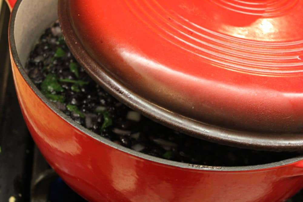 A circular red Dutch oven filled with simmer Mexican black beans with the lid set on top slightly askew.