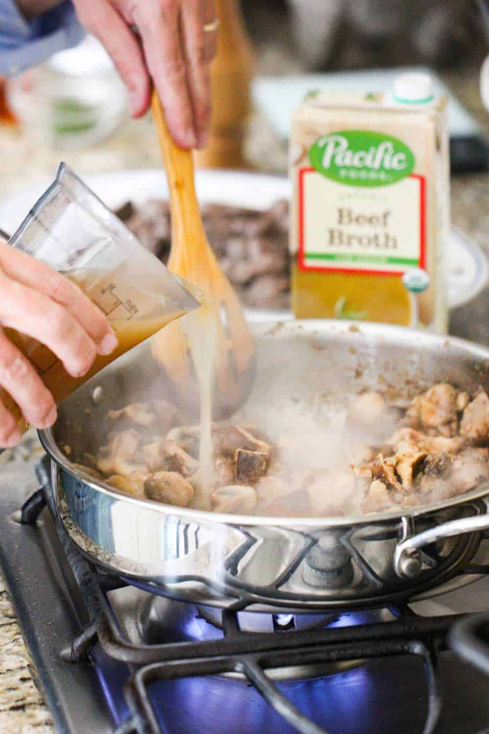 Beef broth being poured into a skillet of gourmet beef stroganoff.