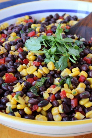 Black bean and Sweet Corn Salad in a white patterned bowl with a wood spoon and a blue napkin behind it