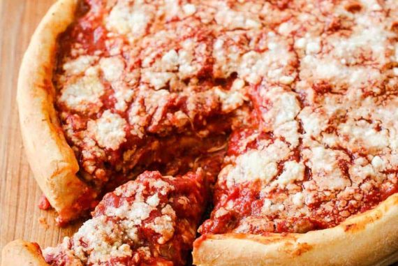 A Chicago-Style Deep Dish Pizza on a cutting board with a slice pulled out next to Parmesan cheese.