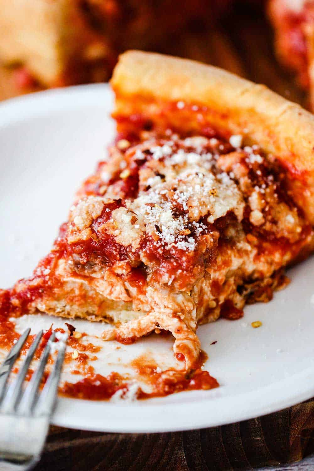 A slice of Chicago-style deep dish pizza on an individual plate with a bite taken out.