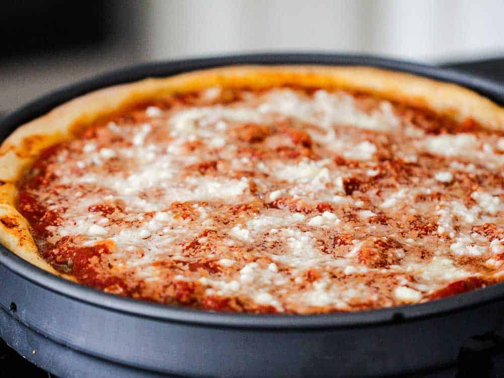 A baked deep-dish pizza in a pizza pan.