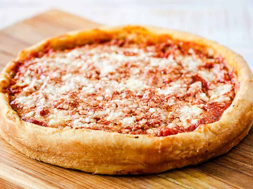 A fully cooked Chicago-style deep dish pizza on a cutting board.