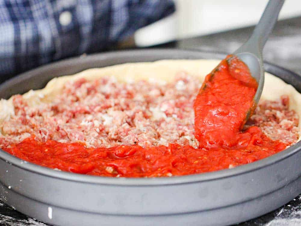 A spoon ladling pizza sauce over sausage in a deep dish pizza pan.