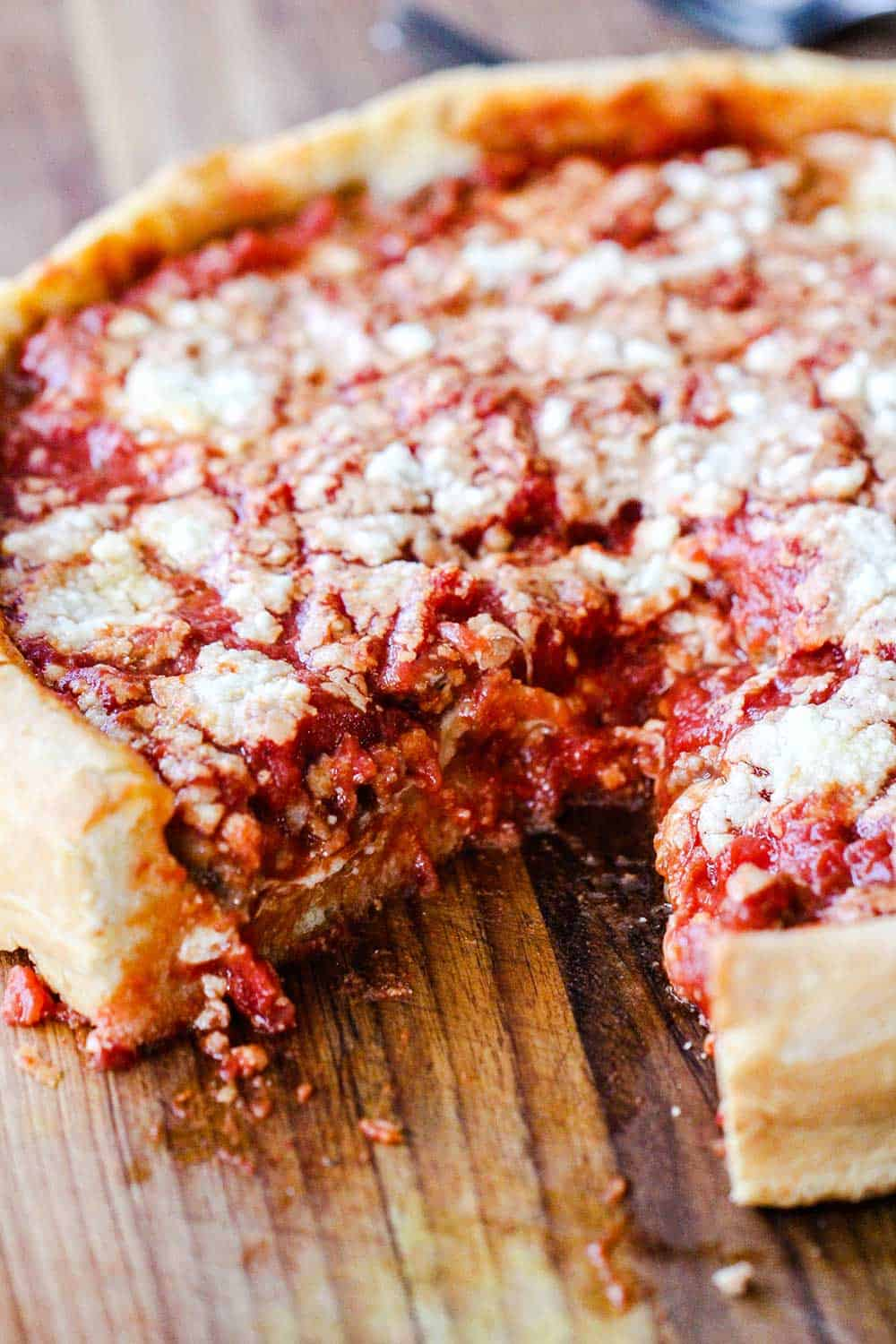 A deep dish pizza with a slice missing on a cutting board.