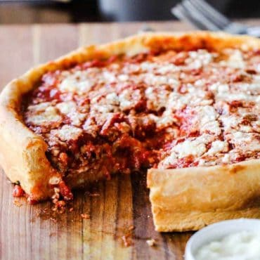 A Chicago-style deep dish pizza with a slice missing sitting on a wooden cutting board.