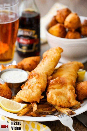 A plate of English fish and chips with a bowl of hush puppies and a glass of beer in the background.