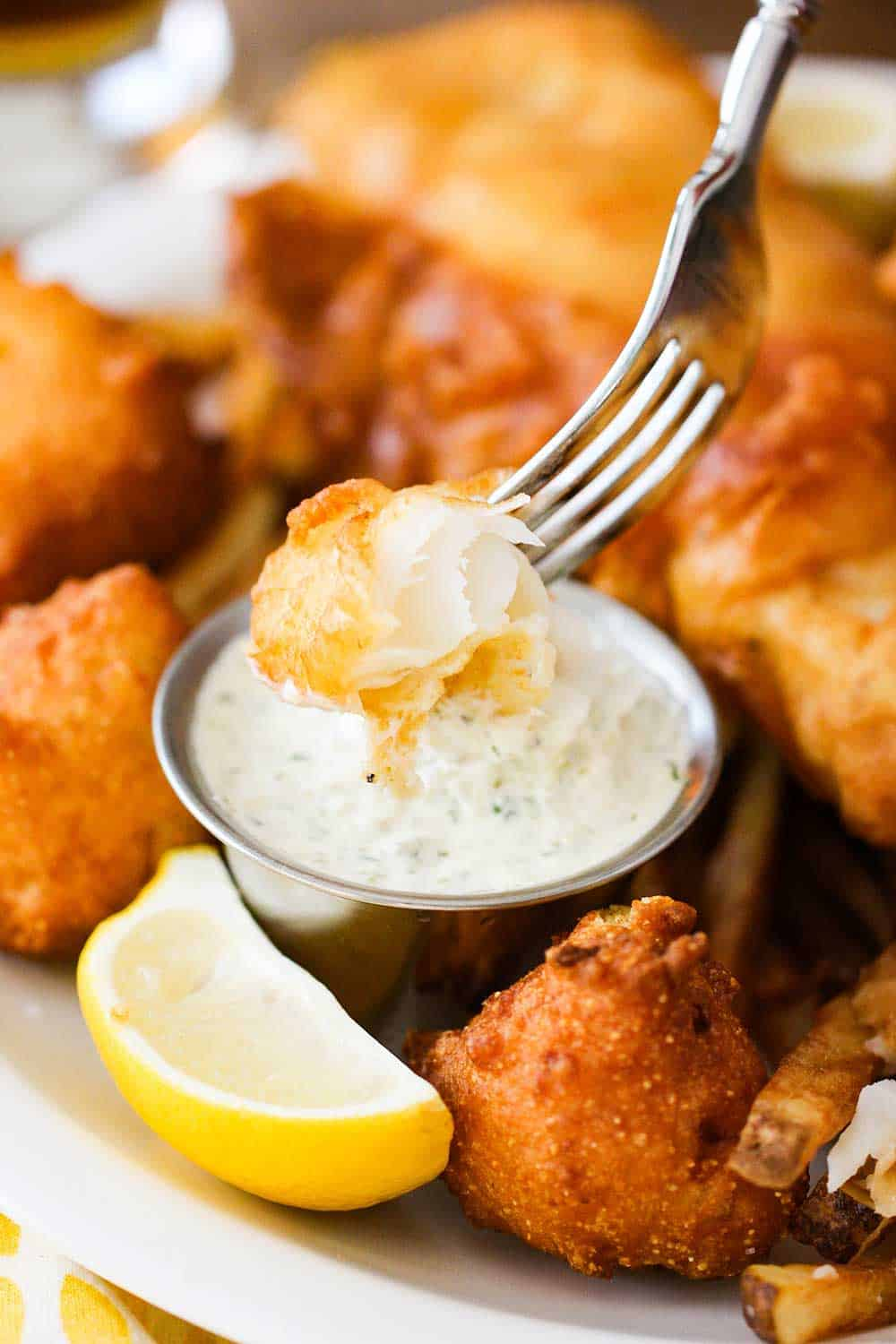 A piece of fried fish in a fork dipped into homemade tartar sauce.