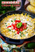 A cast-iron skillet filled with Mexican cream corn topped with crumbled queso fresco, chopped tomatoes, and chopped cilantro.