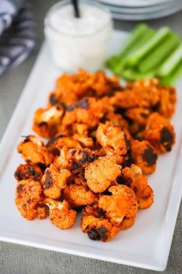 A rectangular white serving platter filled with buffalo cauliflower bites sitting next to a bowl of blue cheese dressing.