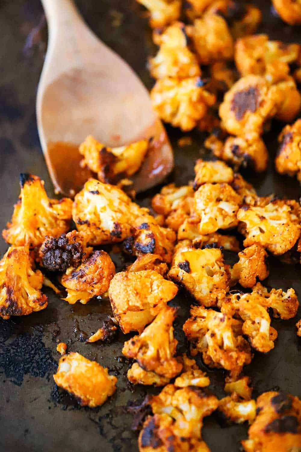 A baking dish filled with buffalo cauliflower bites with a wooden spoon inserted in the middle of them.