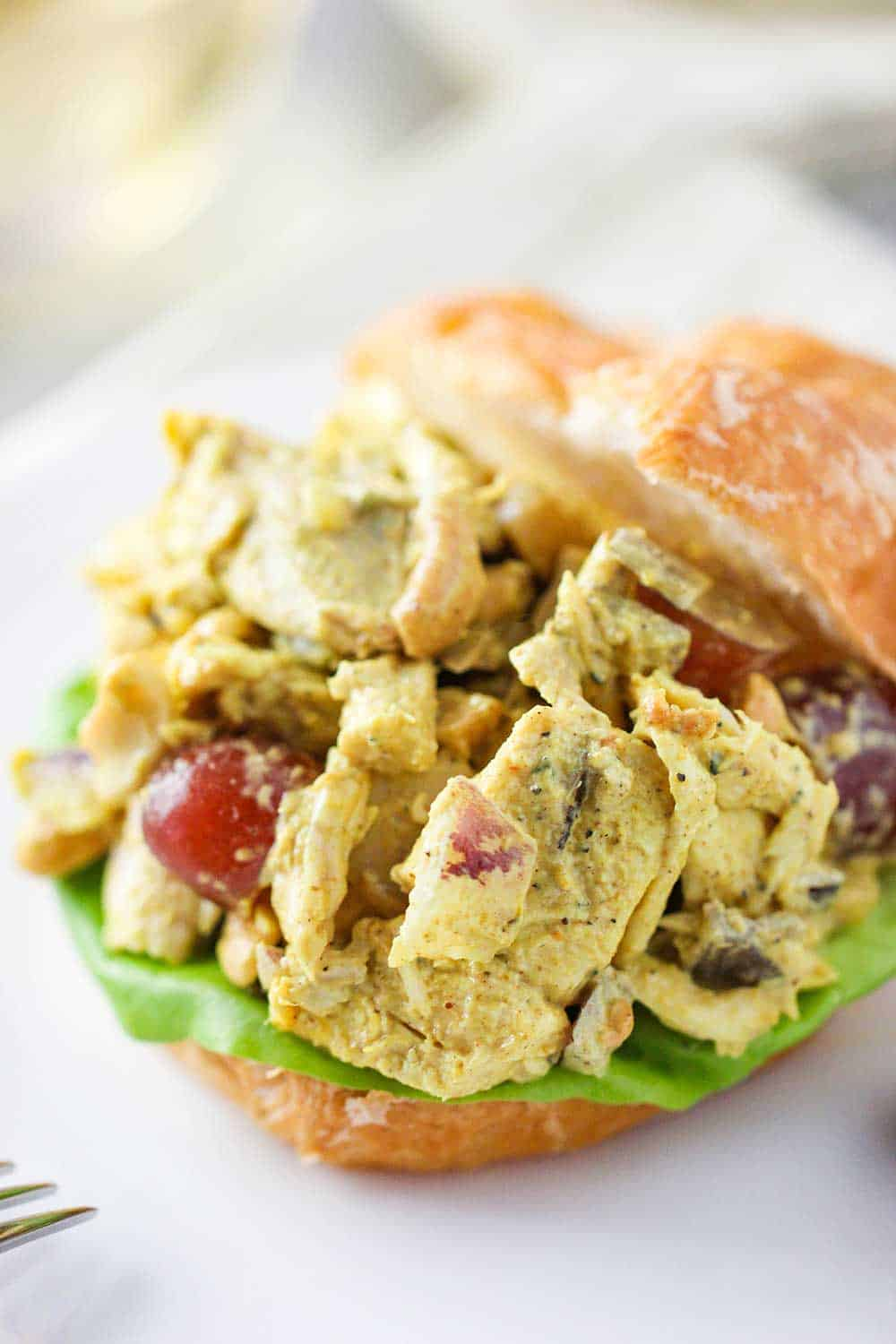 A close-up view of curry chicken salad between two croissant halves on a white plate.