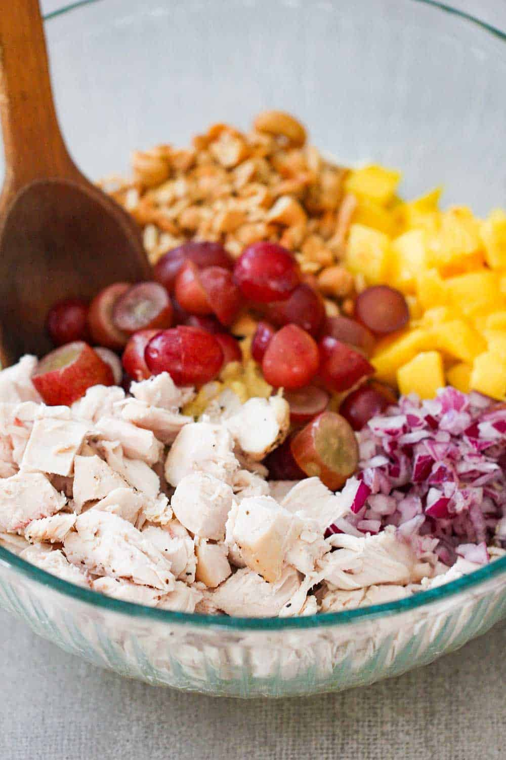 A large glass bowl of cooked cubed chicken, grapes and mango for chicken salad.