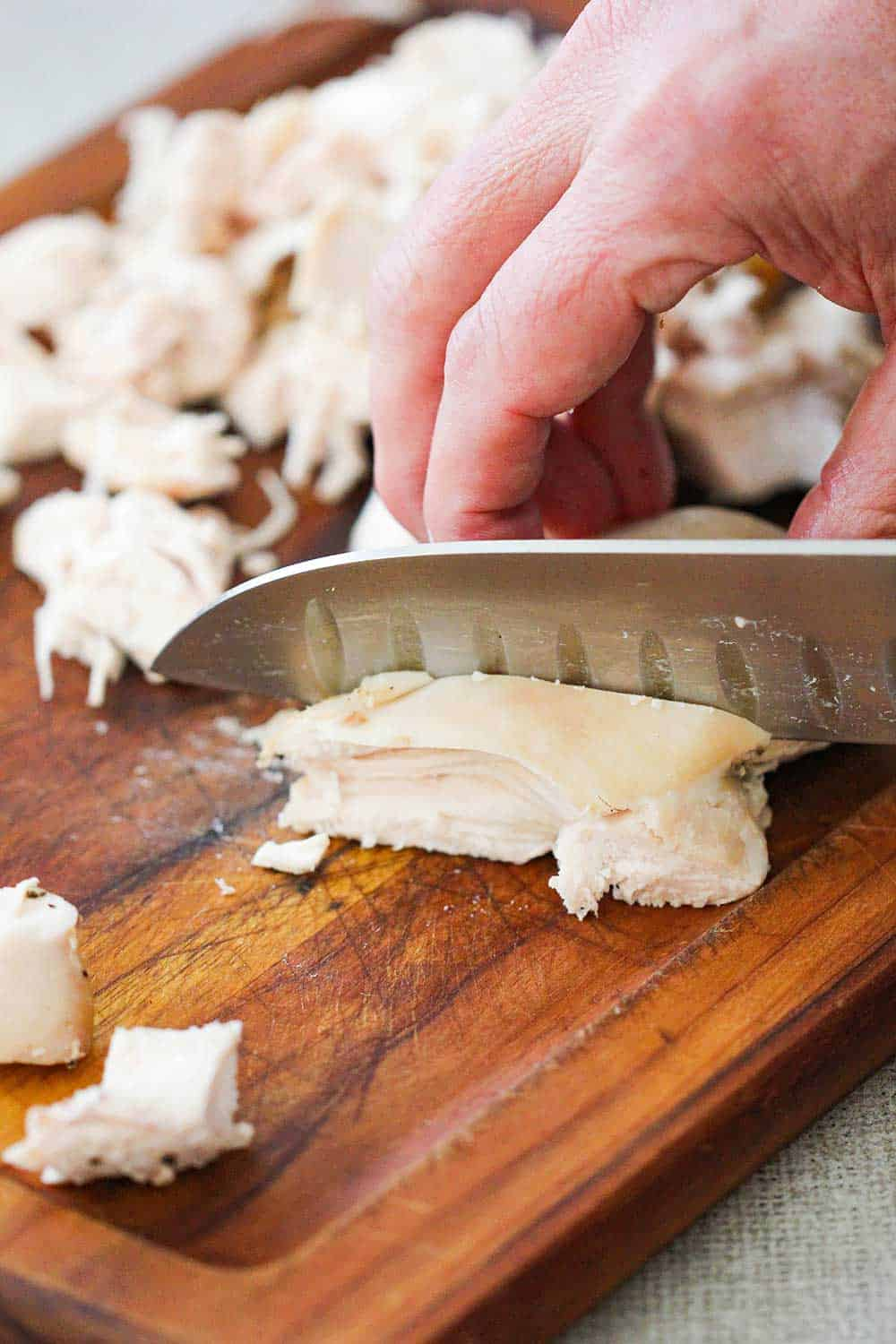 A hand using a large chef's knife to cube cooked chicken on a cutting board.
