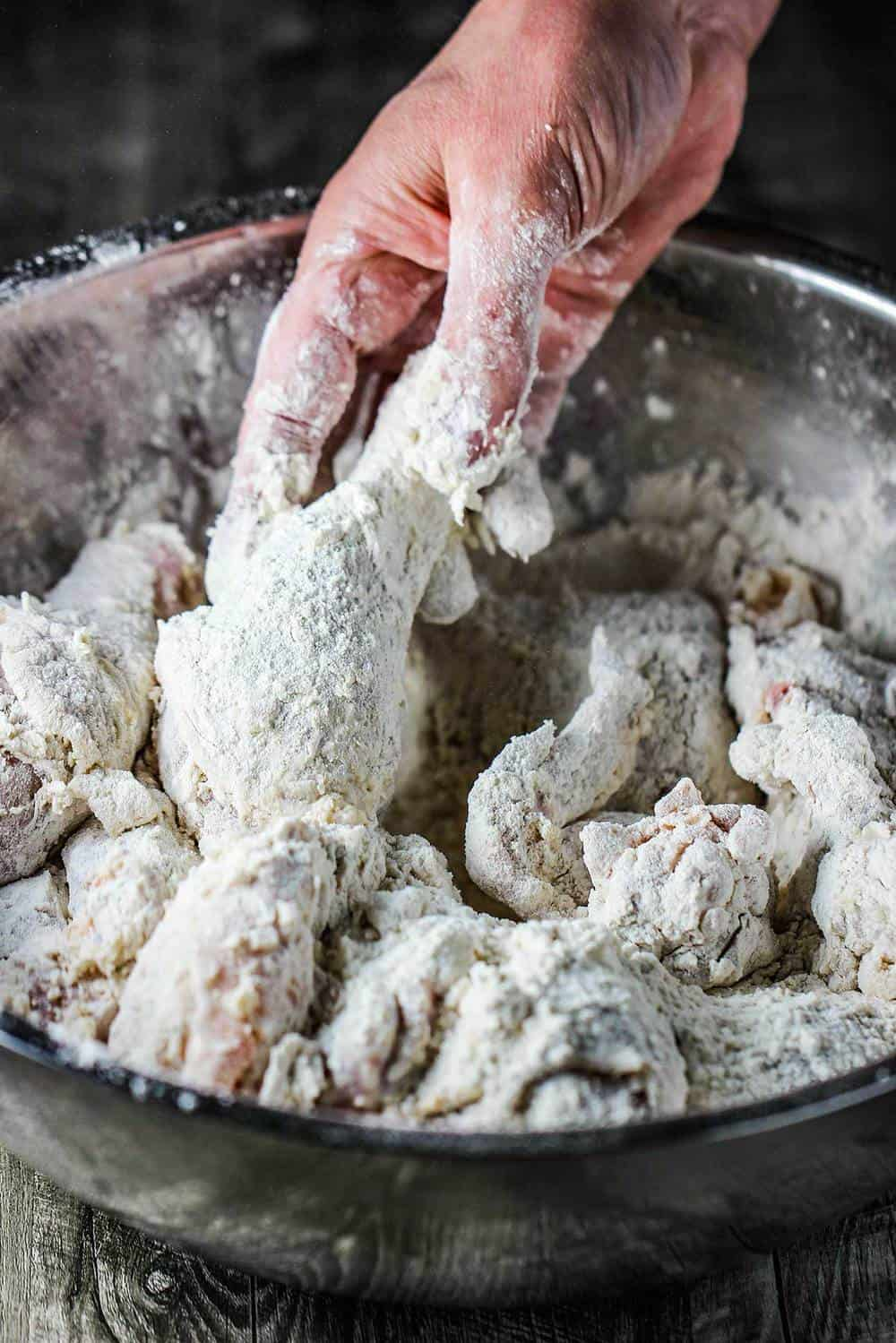 A hand hold a piece of chicken dredged in flour for fried chicken