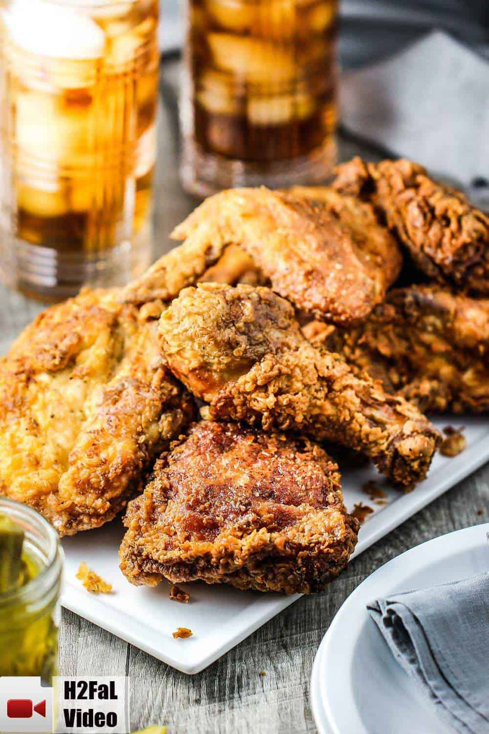 Southern Fried Chicken on a white platter with a glass of iced tea nearby