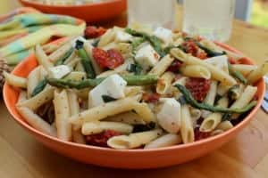 Pasta salad with sauteed asparagus and sun dried tomatoes and basil