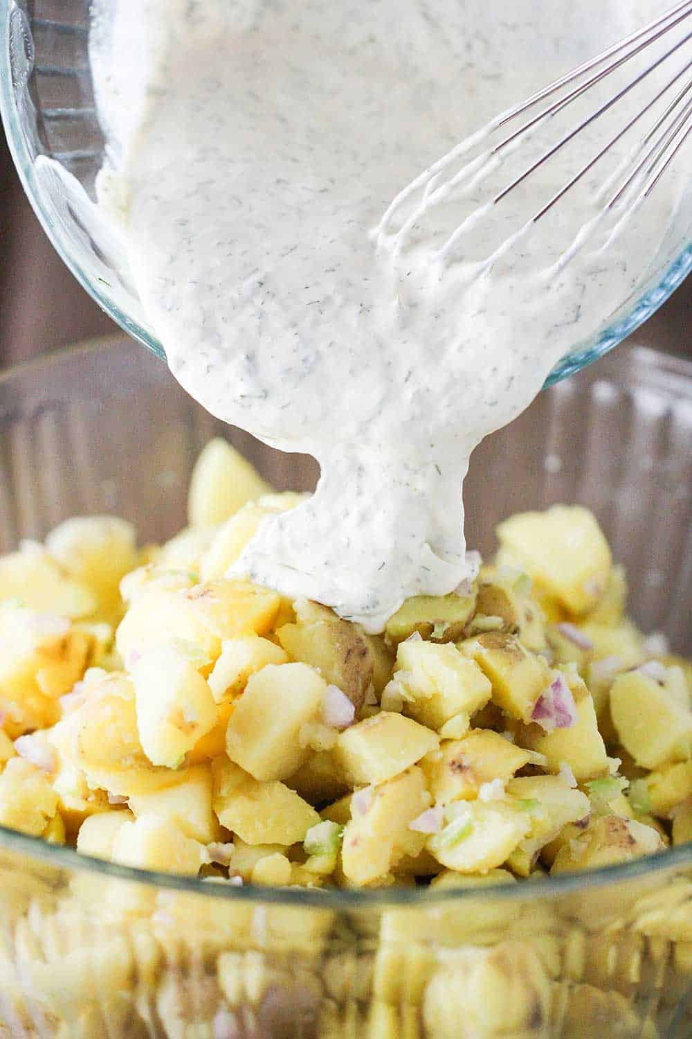 Dill and dijon dressing being pour onto cooked potatoes for potato salad.