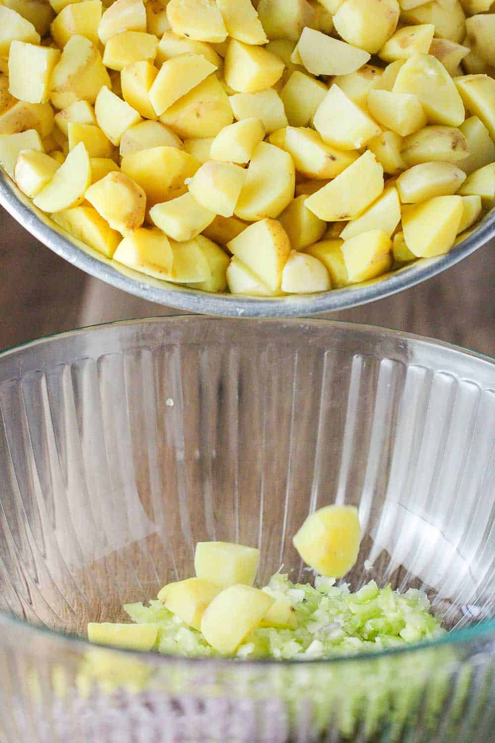 Cooked diced potatoes dropping into a glass bowl with chopped celery. and onion.