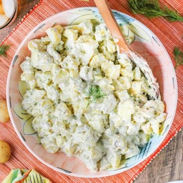 Best-ever potato salad in a large pink bowl with a wooden spoon.