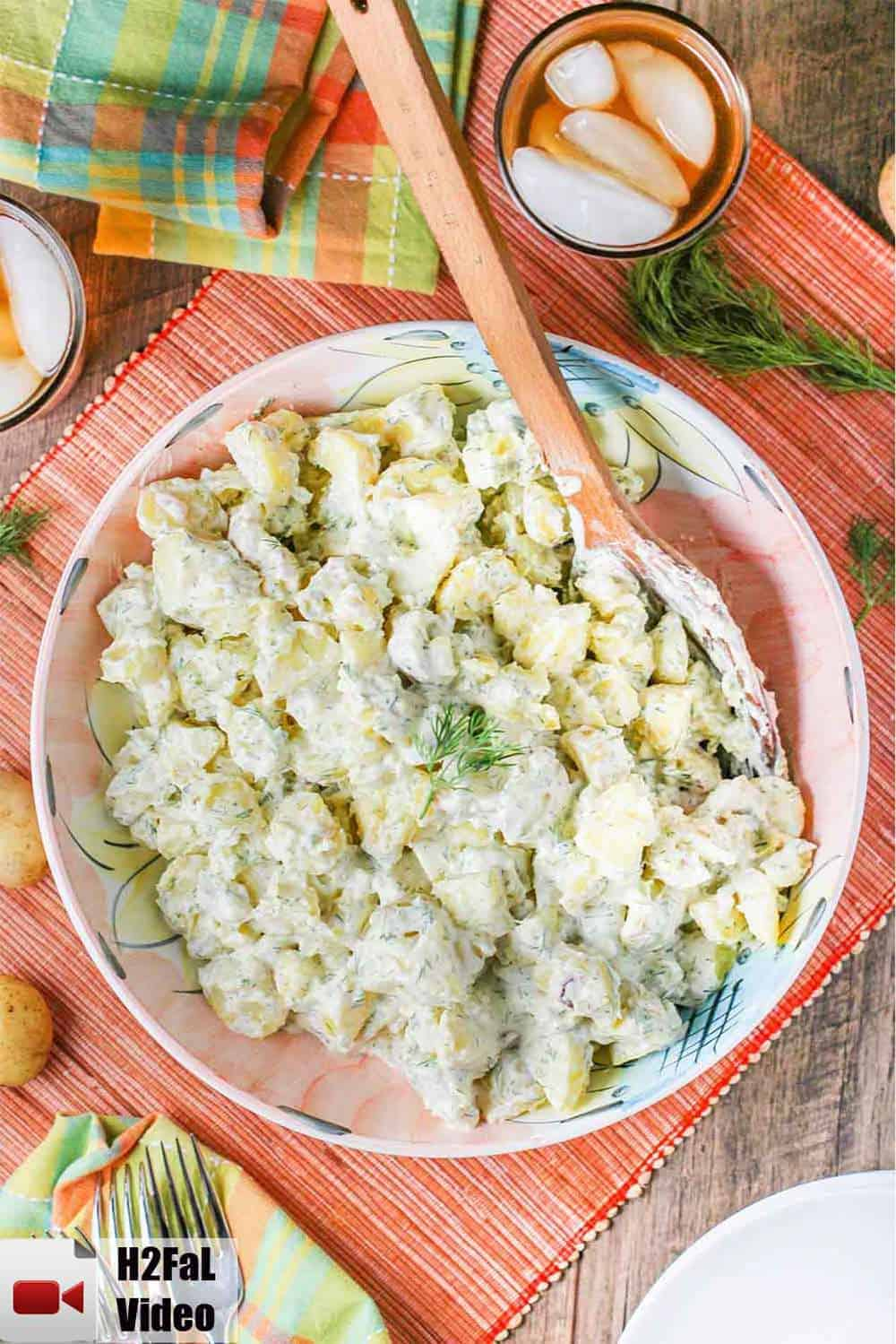 Creamy potato salad in a large pink bowl with a wooden spoon.