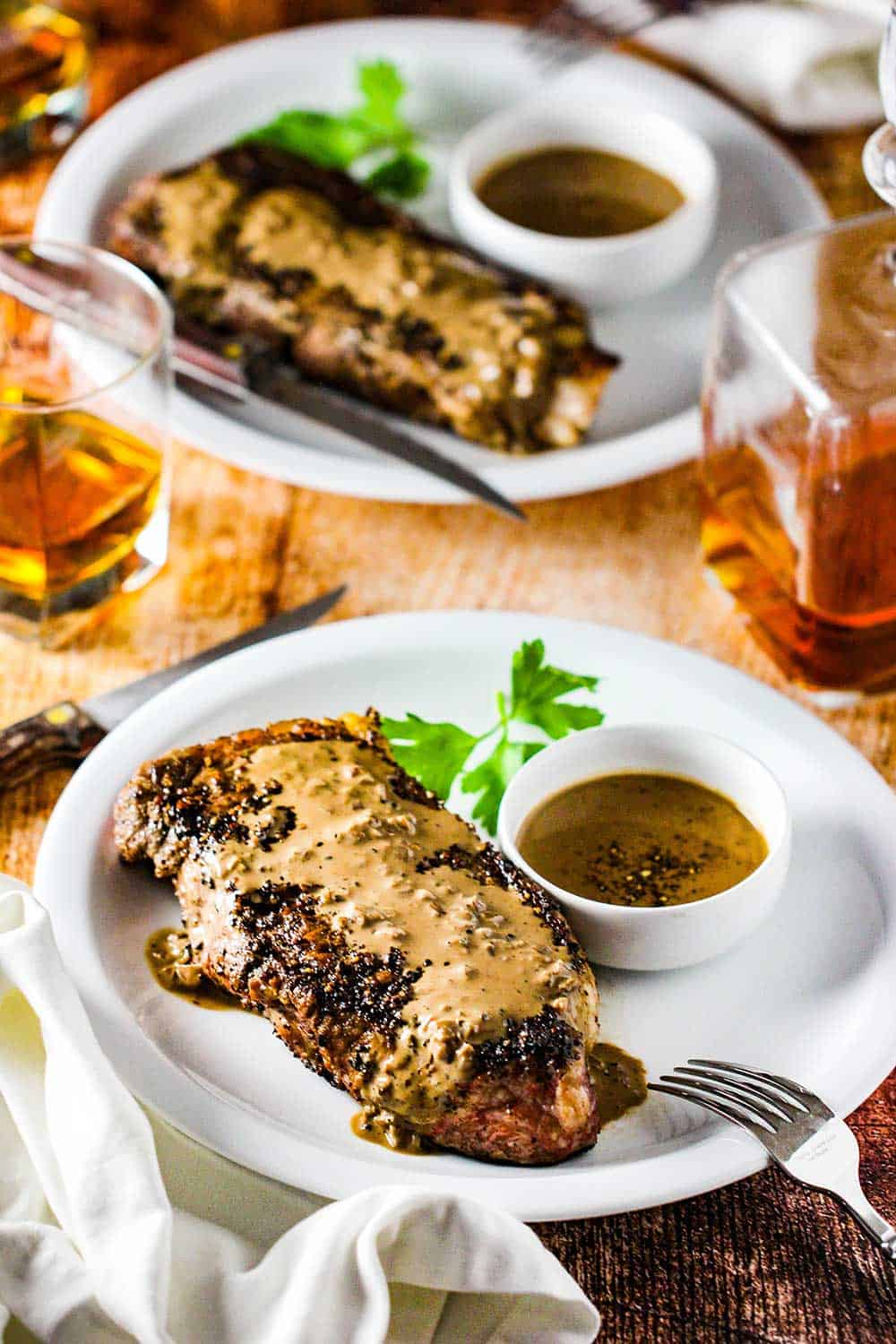 Serve the steak au poivre on a white plate with extra sauce on the side.