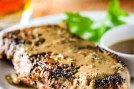 Steak au Poivre on a white plate with a fork nearby.