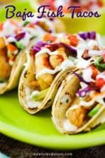 A close up view of three Baja fish tacos on a bright green platter.