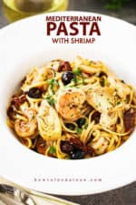 A white bowl with a large edge holding Mediterranean pasta with shrimp.