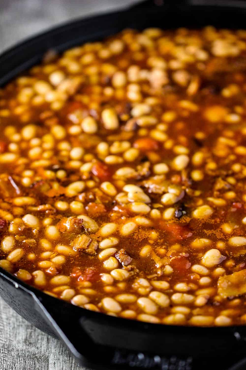 Pre-cooked beans in a sauce in a large cast iron skillet for Southern Baked Beans.