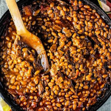 Southern baked beans in a cast iron skillet with a wooden spoon.